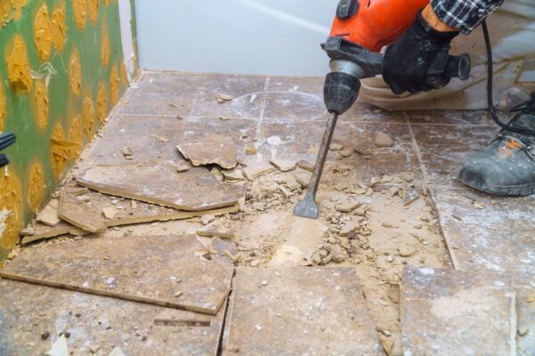 Worker remove, demolish old tiles in a bathroom with jackhammer